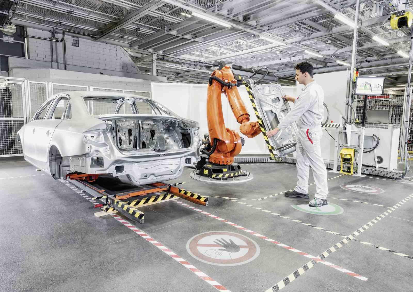 Nello stabilimento Audi si stanno testando continuamente nuove tecnologie di produzione. Come questo robot di assistenza che lavora fianco a fianco con l'addetto al montaggio di linea (in questa immagine il portellone). Il compito del robot è posizionare perfettamente il pezzo nello spazio previsto rispettandone le tolleranze, quello dell'addetto è fissarlo in maniera definitiva