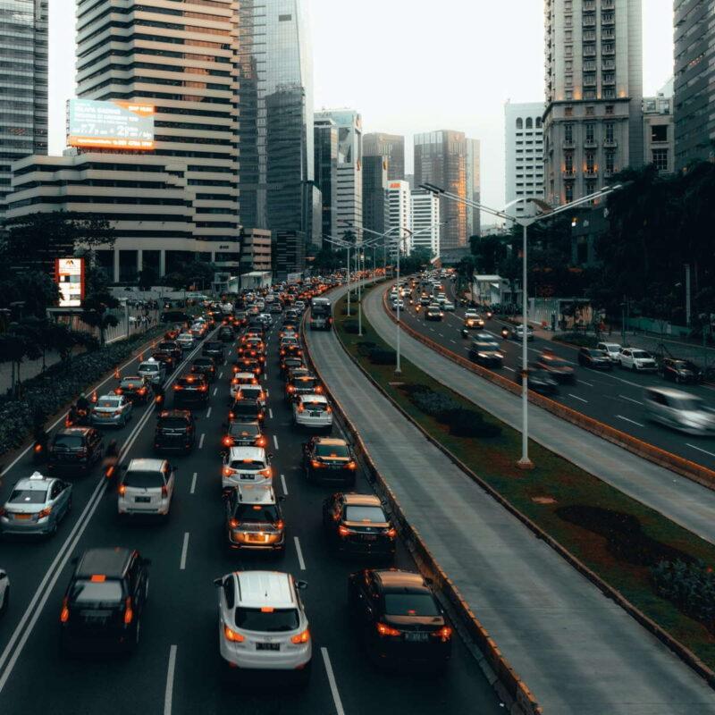 Immagine di auto in coda in una via tra grattacieli